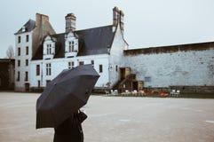 Frau mit dem Regenschirm, der das Schloss von Nantes am regnerischen Tag - Frankreich schaut - Nantes, FRANKREICH - NOVEMBER 2018 lizenzfreies stockbild