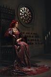 Frau mit dem roten Haar, das auf einem Thron sitzt Stockfotos