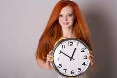 Frau mit dem roten Haar, das eine große Uhr hält Stockfoto