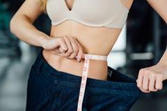 Frau mit dem roten Haar zeigt ihr Gewichtsverlust Lizenzfreie Stockfotografie