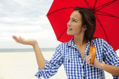 Frau mit dem roten Regenschirm, der den Regen berührt Stockbild