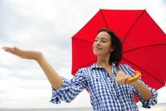 Frau mit dem roten Regenschirm, der den Regen berührt Lizenzfreie Stockfotos