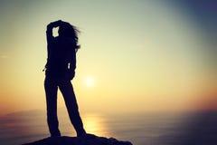 Frau mit dem Rucksack, der auf windiger Küste des Sonnenaufgangs steht Stockbilder