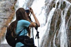 Frau mit dem Rucksack, der Foto des Wasserfalls macht lizenzfreies stockbild