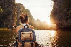 Frau mit dem Rucksack, der mit dem Boot Sonnenuntergang unter m genießend reist stockfoto