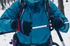 Frau mit dem Rucksack, der Trekking poole im Winterwald justiert stockfoto