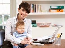 Frau mit dem Schätzchen, das vom Haus unter Verwendung des Laptops arbeitet stockfotografie