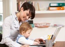 Frau mit dem Schätzchen, das vom Haus unter Verwendung des Laptops arbeitet Stockbild