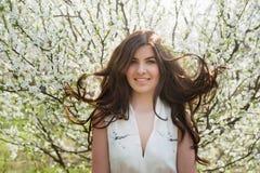Frau mit dem schönen Haar im üppigen Frühlingsgarten lächelnd und freuend, Schönheit, Make-up, Haar stockfotografie