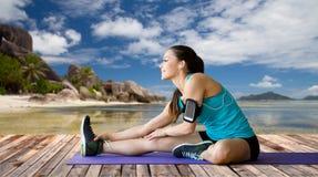 Frau mit dem Smartphone, der Bein auf Matte ausdehnt Lizenzfreie Stockfotos