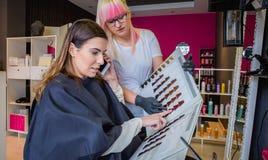 Frau mit dem Smartphone, der eine Haarfärbemittelpalette schaut lizenzfreies stockfoto