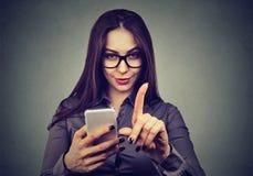 Frau mit dem Smartphone, der keine Aufmerksamkeit mit Fingergeste zeigt Elterliches Bedienkonzept Stockfotografie