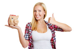 Frau mit dem Sparschwein, das Daumen hochhält Stockfotografie
