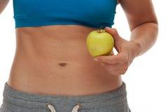 Frau mit dem sportiven Körper, der einen frischen Apfel hält stockfoto