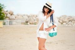 Frau mit dem Strandhut, der durch den Ozean am exotischen Erholungsort sich entspannt Stockbilder