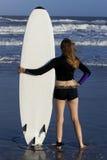 Frau mit dem Surfbrett, das Ozean betrachtet stockfotos