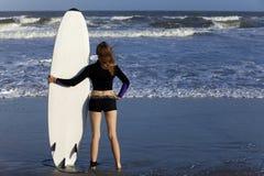 Frau mit dem Surfbrett, das Ozean betrachtet stockfotografie