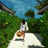 Frau mit dem Taschen- und Sonnenhut, der geht auf den Strand zu setzen Lizenzfreies Stockfoto
