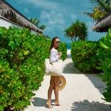Frau mit dem Taschen- und Sonnenhut, der geht auf den Strand zu setzen Stockfotos