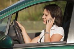 Frau mit dem Telefon, das Auto antreibt lizenzfreie stockbilder