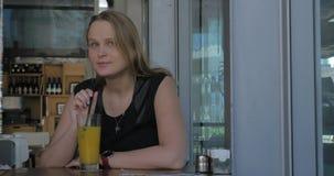 Frau mit dem wehmütigen Blick, der Saft im Café isst stock footage