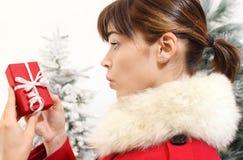 Frau mit dem Weihnachtsgeschenk, überrascht Stockfoto
