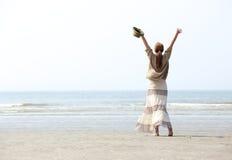 Frau mit den angehobenen Armen am Strand Lizenzfreies Stockfoto