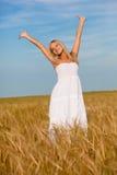 Frau mit den angehobenen Händen auf Weizenfeld Stockfoto