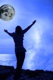 Frau mit den angehobenen Händen eine Welle und ein Vollmond Lizenzfreie Stockfotografie
