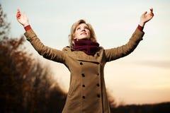 Frau mit den Armen angehoben gegen einen Himmel Stockfotografie