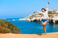 Frau mit den Armen hob oben nahe dem Meer an Stockbild