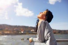Frau mit den Augen geschlossen, das Meer genießend Stockfoto