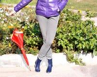 Frau mit den blauen Gummiregenstiefeln, die roten Moderegenschirm halten Lizenzfreie Stockfotografie