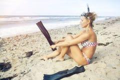 Frau mit den Flippern, die auf dem Strand sitzen Stockfoto