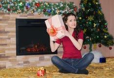 Frau mit den Geschenken, die durch den Kamin sitzen Lizenzfreie Stockfotografie