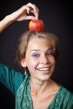 Frau mit den gesunden Zähnen und Apfel auf Kopf stockfoto