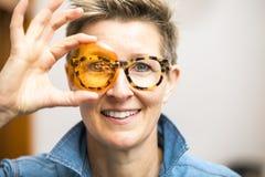 Frau mit den Gläsern, die durch orange Glas schauen stockfoto
