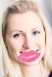 Frau mit den großen Papierlippen vor ihrem Mund Stockbild