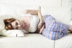 Frau mit den Händen auf ihrer leidender Magenklammer und -zeitraum des Bauches oder des Bauches schmerzen Stockbilder