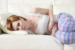 Frau mit den Händen auf ihrer leidender Magenklammer und -zeitraum des Bauches oder des Bauches schmerzen Stockfotografie