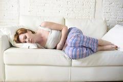 Frau mit den Händen auf ihrer leidender Magenklammer und -zeitraum des Bauches oder des Bauches schmerzen Stockfoto
