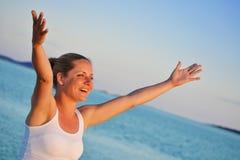Frau mit den Händen, die oben Freude auf dem Strand ausdrücken Lizenzfreie Stockfotografie