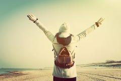 Frau mit den Händen, die oben Retro- Rucksack auf dem Strand tragen lizenzfreies stockfoto