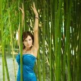 Frau mit den Händen oben in einem grünen Bambusgarten stockfotografie
