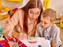 Frau mit den Kindern, die herein farbiges Papier und Kleber halten stockbild
