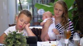 Frau mit den Kindern, die im Straßencafé sich entspannen stock footage
