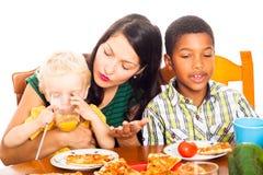 Frau mit den Kindern, die Pizza zu Mittag essen Lizenzfreie Stockfotografie