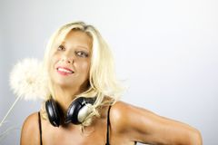 Frau mit den Kopfhörern, die mit Löwenzahn spielen Stockbild