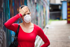 Frau mit den Kopfschmerzen, die eine Gesichtsmaske tragen Lizenzfreie Stockbilder