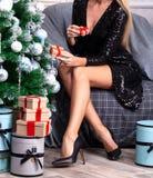 Frau mit den langen Beinen, die durch den Weihnachtsbaum sitzen stockbilder